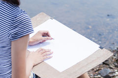 Kvinnakonstnärdanande skissar något på flodstranden Arkivfoton