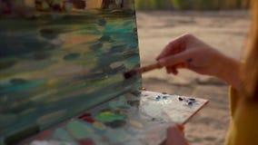 Kvinnakonstnären blandar olje- målarfärger i paletten på staffli som hon är i den öppna luften lager videofilmer