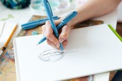Kvinnakonstnären räcker teckningen med stelnar bläckpennan i sketchbook royaltyfri bild
