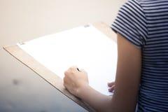 Kvinnakonstnärteckning något på flodstranden Arkivfoto