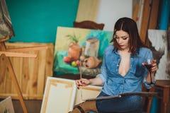 Kvinnakonstnär som målar en bild i en studio Arkivfoton