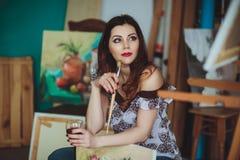 Kvinnakonstnär som målar en bild i en studio Arkivfoto