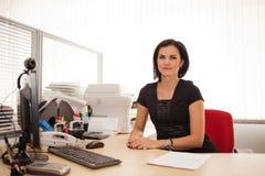 Kvinnakontorsarbetare på skrivbordet Arkivbilder