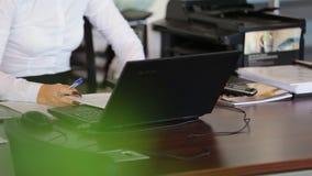 Kvinnakontorschef som arbetar med dokument Nära bärbara datorn stock video