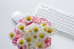 Kvinnakontorsskrivbord med blomningblommor Arkivfoto