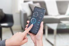 Kvinnakontrollljus i vardagsruminre med smart hem- kontroll app på moderna mobila enheter royaltyfri bild