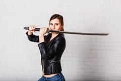 Kvinnakrigaren i ett svartläderomslag med ett tungt svärd i hans händer fotografering för bildbyråer