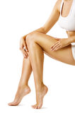 Kvinnakroppen lägger benen på ryggen skönhet, modellen Sitting på vit, handlagbenhud arkivbild