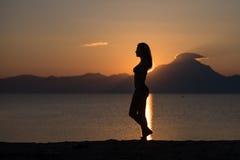 Kvinnakroppkontur på soluppgång på stranden Fotografering för Bildbyråer