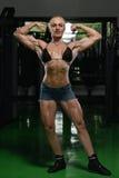 Kvinnakroppsbyggare som böjer muskler royaltyfria foton