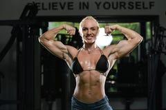 Kvinnakroppsbyggare som böjer muskler arkivfoto