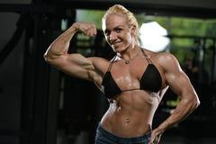 Kvinnakroppsbyggare som böjer muskler royaltyfri foto