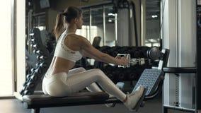 Kvinnakroppsbyggaresammanträde på instruktörutrustning för lyftande vikter i idrottshallklubba stock video