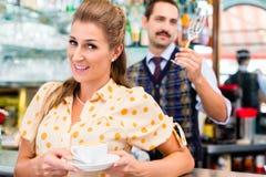 Kvinnakund i cafeteria som dricker koppen av cappuccino Royaltyfri Foto