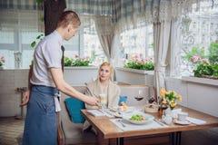 Kvinnakund som beställer espresso eller cappuccino på stångräknaren i restaurang royaltyfria bilder
