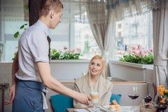 Kvinnakund som beställer espresso eller cappuccino på stångräknaren i restaurang royaltyfri foto