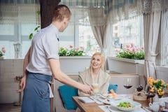Kvinnakund som beställer espresso eller cappuccino på stångräknaren i restaurang arkivbilder