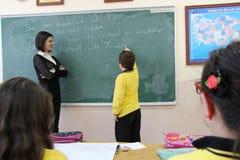 Kvinnaläraren i klassrumet Arkivfoto