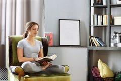 Kvinnaläsebok hemma i vardagsrummet Arkivfoto