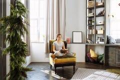 Kvinnaläsebok hemma i vardagsrummet Royaltyfri Fotografi