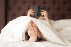 Kvinnaläsebok i morgonen på hennes sovrum Royaltyfria Foton