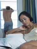 Kvinnaläsebok i säng med mannen i bakgrund Fotografering för Bildbyråer