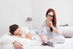 Kvinnaläsebok i säng och man som sover bredvid henne Arkivbilder