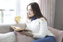 Kvinnaläsebok med koppen kaffe som är hemmastadd i vardagsrummet royaltyfria foton