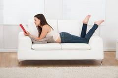 Kvinnaläsebok, medan ligga på soffan Arkivbild