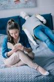 kvinnaläsebok, medan vila på säng med skyltdockan arkivfoto