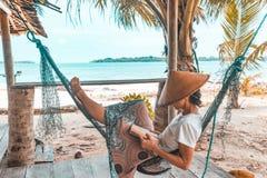 Kvinnaläsebok på den tropiska stranden för hängmatta, verkligt folk som får i väg från all den, traditionell södra asiatisk hatt, fotografering för bildbyråer