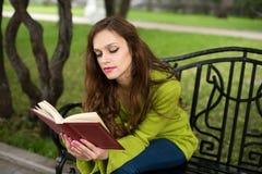 Kvinnaläsebok på parkera Royaltyfri Foto