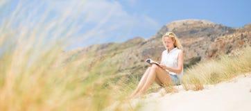 Kvinnaläsebok som tycker om solen på stranden Arkivbild