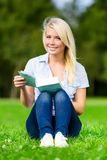 Kvinnaläseboken sitter på det gröna gräset arkivbilder