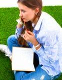 Kvinnaläseboken sitter på det gröna gräset royaltyfria foton