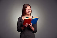 Kvinnaläsning boka och le Arkivfoton