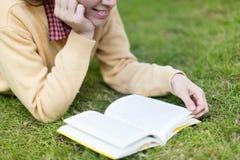 Kvinnaläsning en boka royaltyfri foto