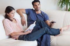 Kvinnaläsning en boka fördriver som henne, håller ögonen på fiancen TV:N Arkivfoton