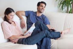 Kvinnaläsning en boka fördriver som henne, håller ögonen på makan televisionen Royaltyfri Foto