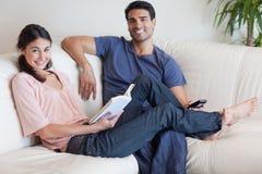 Kvinnaläsning en boka fördriver som henne, håller ögonen på makan TV:N Arkivbild