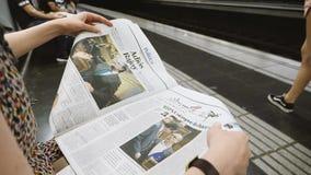 Kvinnaläsning i Barcelona tunnelbanastation den LaVanguardia fria pressen lager videofilmer