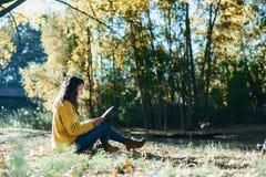 Kvinnaläsning i den utomhus- hösten arkivfoto