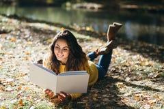 Kvinnaläsning i den utomhus- hösten royaltyfria foton