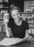 Kvinnaläsning i kafét med en kopp kaffe som är svartvit royaltyfria bilder