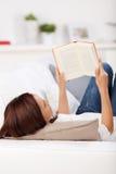 Kvinnaläsning på en soffa arkivbild