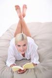 Kvinnaläsning på sängen Royaltyfria Bilder