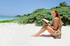 Kvinnaläsning på stranden Arkivfoton