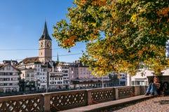 Kvinnaläsning under trädet och St Peter Pfarrhaus Church i Zurich den gamla staden Altstadt arkivbild