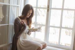 Kvinnaläsning vid fönstret royaltyfri bild