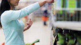 Kvinnaläsningetiketten på olivoljaflaskan på shoppar lager videofilmer